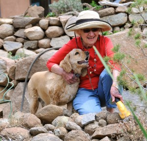 An avid gardener at her Piños Altos home, Port Laureate Bonnie Maldonado is joined by Murphy, one of three rescue dogs and two cats owned by Bonnie and her husband Librado. (Photo by Harry Williamson)